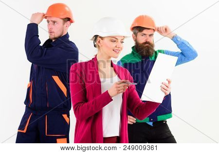 Female Boss Concept. Woman In Hard Hat With Busy Face Manages Mens Team Of Builders, Defocused. Team