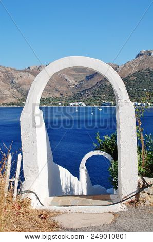 TILOS, GREECE - JUNE 12, 2018: A white archway frames Livadia harbour on the Greek island of Tilos. The Dodecanese island has a population of around 780 people.