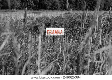 Red Painted Sign In Estonian Language Saying Private Land. Black And White Picture.
