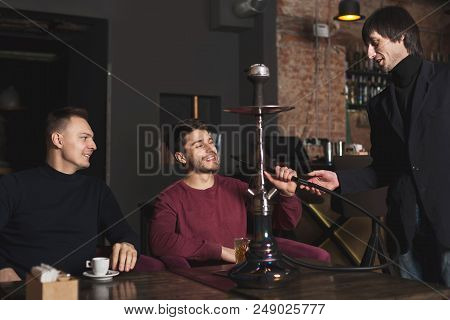 Two Confident Businessmen Drinking Whiskey And Ordering Hookah, Having Informal Business Meeting At
