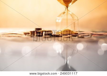 Reflection Of Brown Sand Running Through The Shape Of Modern Hourglass On Glowing Table With Currenc