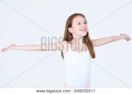 Emotion Face. Joyful Delighted Smiling Child With Her Arms Out Sideways. Little Girl Portrait On Whi
