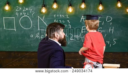 Teacher And Child Turned Back In The Classroom. Boy Listening To The Explanation About Different Sha