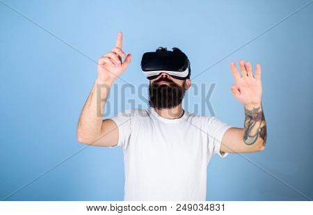 Man With Beard In Vr Glasses, Light Blue Background. Hipster On Busy Face Exploring Virtual Reality