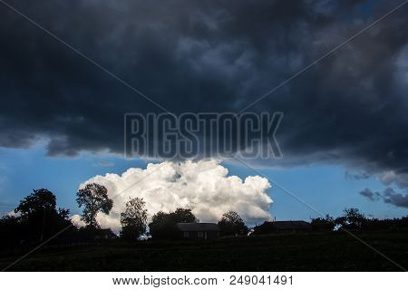 Dark Storm Clouds Over A Small White Cloud. Different Clouds During A Thunderstorm. Dark And Bright