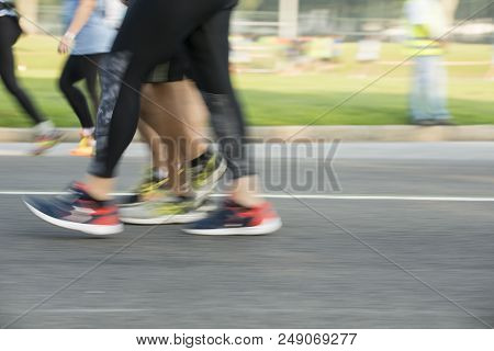 People Running In A Street Race On An Asphalt Surface, With Motion Blur Effect