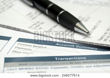 Pen On Top Of Receipts And Bank Statements