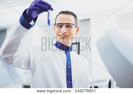 Work with pleasure. Cheerful practitioner raising his arm while looking at test tube poster