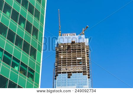 Construction Crane On Building Skyscraper Apartment House, On A Background Of Glass Texture Of Finan