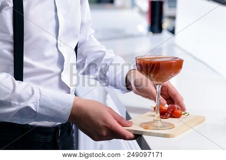 Unidentified Barman Holding Martini Glass With Red Alcoholic Cocktail On The Wooden Board