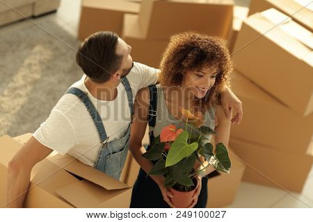Beautiful young couple is carrying boxes to a new home.