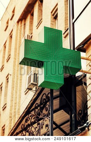 Pharmacy Sign On The Street, Green Medical Cross Pharmacy Sign Or Symbol On The Building Facade View