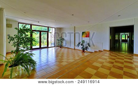 A Hall In A Building With Standing Pots With Green Plants A Picture On The Wall And A Beautiful View