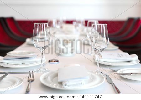 Perspective View Of Table Set With White Dishware And Crystal Clear Wineglasses On White Tablecloth