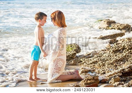 Attractive Pregnant Caucasian Woman With Her Adorable Son At The Mediterranean Beach. Special Mother
