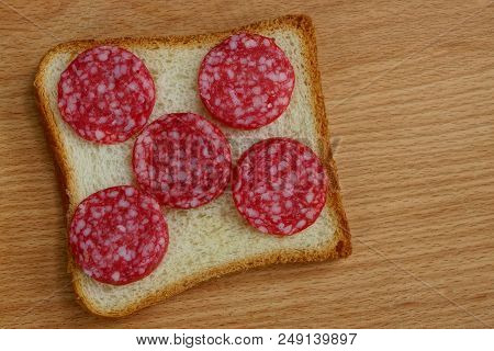 Square Piece Of Bread And Sliced Sausage Salami On A Brown Table
