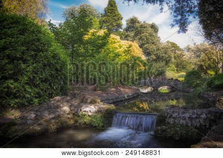 Idyllic Picturesque Summer Landscape River Scene With Beautiful Waterfall And Stone, Bridge. Stereot