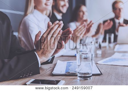 Smiling People Clap Their Hands At Conference. Mobile Phone And Glass Of Water Closeup. Blur Image I