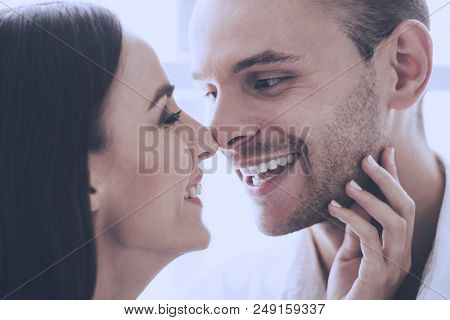 Beautiful Loving Couple Touching Their Noses. Portrait Of Young Handsome Guy With Pretty Girl Lookin
