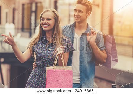Beautiful Young Couple Holding Shopping Bags And Looking Away And Smiling While Walking In Mall. Han