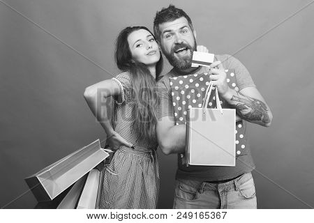 Couple In Love Hugs, Holding Box And Pink Shopping Bags On Green Background. Guy With Beard And Pret