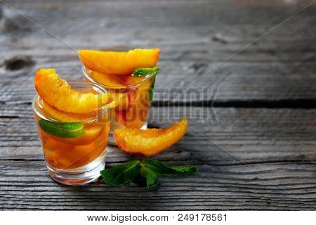 Peach Cocktail Or Tea With Mint On Wooden Background. Closeup.