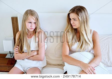 Mother And Daughter Sitting On A Mattress Looking Sad Angry