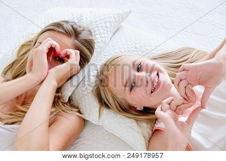 Mother And Daughter Smiling Making Heart Shape From Hand While Lying On Bed At Home