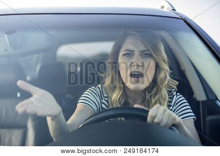 Angry Woman Driving A Car. The Girl With An Expression Of Displeasure Is Actively Gesticulating Behi