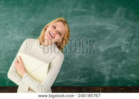 Teacher. Portrait Of Young Smiling Teacher In Classroom. Young Satisfied Professor. Prof With Folder