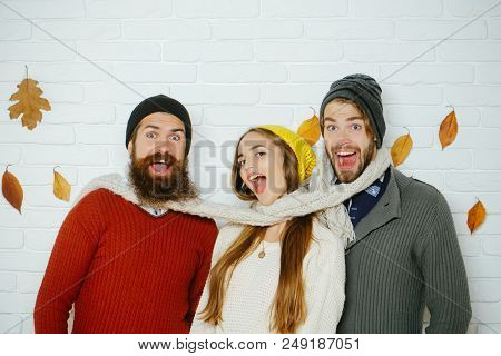 Happy Friends At Autumn Leaves In Scarf And Hat. Girl And Men At Seasonal Brick Wall. Men And Woman,