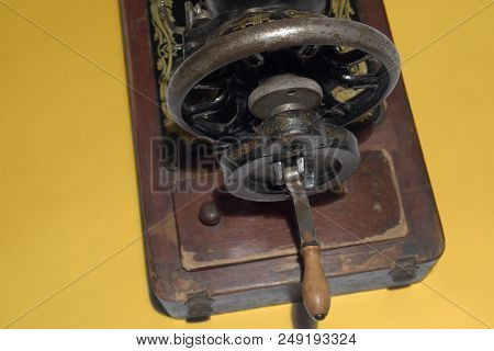 Old Sewing Machine Rear Rotating Mechanism Close-up. Graceful Wheel And Simple Wooden Handle. With C
