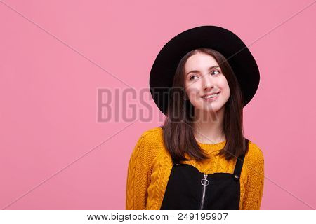 A Good-looking Girl Is Posing In A Cool Black Hat With Wide Brims On The Bright Pink Background.