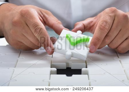 Human Hand Solving Jigsaw Puzzle By Connecting White Piece With Check Mark