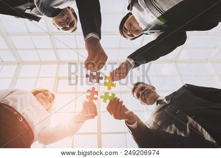 Businessmen Holding And Putting Puzzle Pieces Together. Teamwork And Cooperation Concept. Bottom Vie