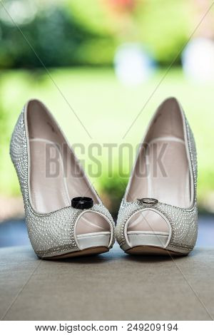 Peep Toe High Heel Shoes Of The Bride Holding The Husband And Wife Wedding Rings On Top.