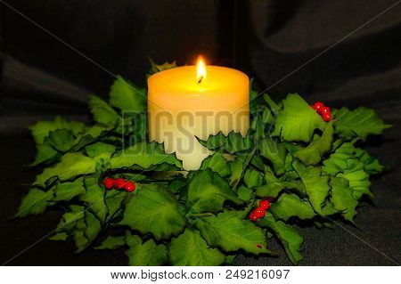 Glowing Candle With Dark Background And Christmas Holiday Decor