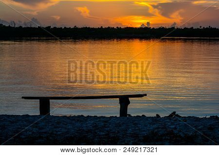 An artsy view of an empty rustic bench in the sunrise  over the intracoastal waterway from the Cove Road park in Port Salerno, Florida.