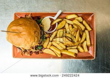 Home Made Hamburger With Lettuce, Cheese, Beef Meat And French Fries Placed On Old Stainless Steel T