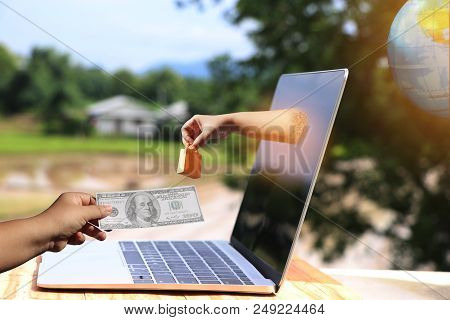 Hand Holding Shopping Paper Bag Came Out From Laptop Screen On Wooden Table Outdoor And Another Hand