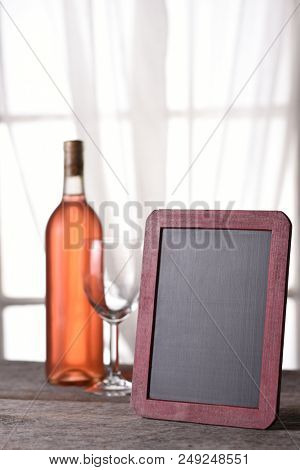 A bottle of blush wine with a blank menu board, on a rustic wood table in front of a window. Perfect for a Wine Menu or Wine Tasting announcement.
