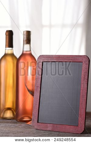 A bottle of blush and chardonnay wine with a blank menu board, on a rustic wood table in front of a window. Perfect for a Wine Menu or Wine Tasting announcement.