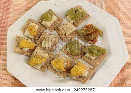 Baked Whole Wheat Crackers Topped With Cheddar Cheese, Guacamole, Horseradish, Mustard And Hot Sauce