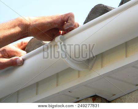 Contractor Installing Plastic Roof Gutter. Plastic Roof Guttering Renovation, Rain Guttering Repair