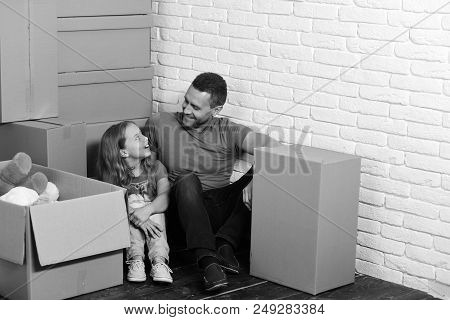 New Home And Family Concept. Girl And Man With Smiling Faces In Room On White Brick Wall Background.