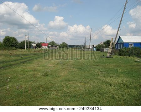 Summer Rural Landscape. In The Middle Of The Street A Wide Clearing On Which The Lawn Grows. Posts W