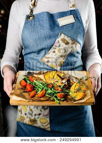 Unidentified Waiter Giving Wooden Board With Delicious Fish Served With Tomatoes, Lemon And Herbs