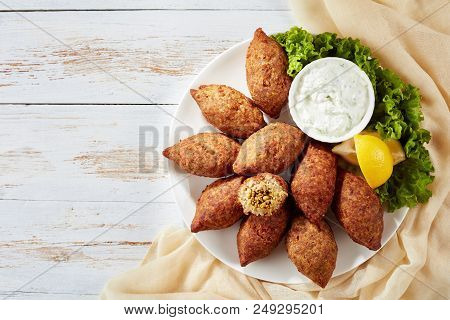 Delicious Fried Kibbeh With Yogurt Sauce In A Bowl Served On A Plate With Lettuce And Lemon Slices O