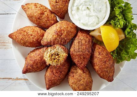 Delicious Fried Kibbeh With Yogurt Sauce In A Bowl Served On A White Plate With Lettuce And Lemon Sl