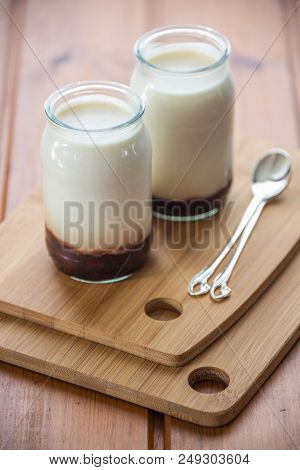 Two Pots Of Homemade Yoghurt With Jam On Wood Boards